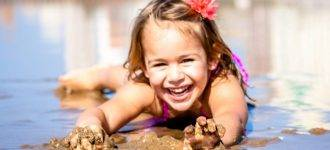 Girl playing in the mud after eye exam in Laguna Beach
