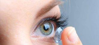 Woman putting in contact lens in Laguna Beach