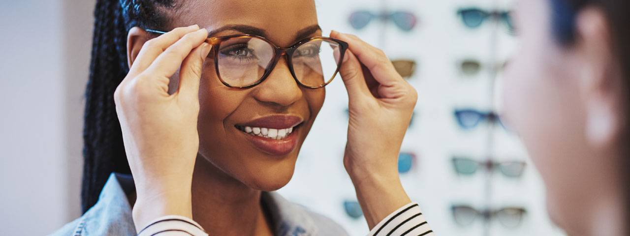 woman trying on glasses, designer eyewear at True Vision Eye Care in Morrisville, North Carolina