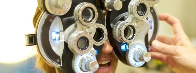 Eye doctor, woman using a phoropter in Plano, TX