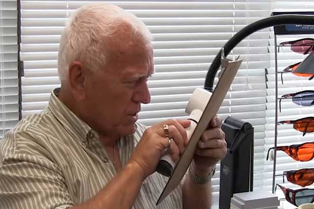 Man Using Low Vision Aid to Read Chart