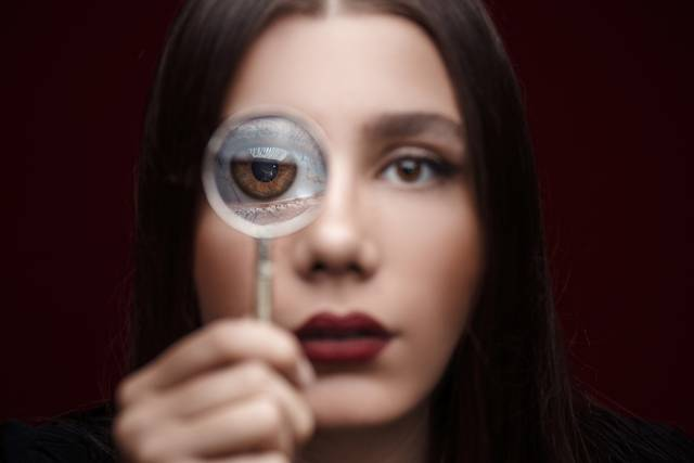 optometrist, woman experiencing dry eye, holding magnifying glass in Tulsa, OK