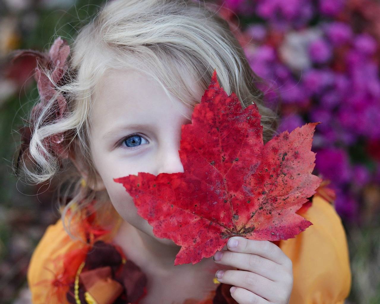 child covering one eye with leaf