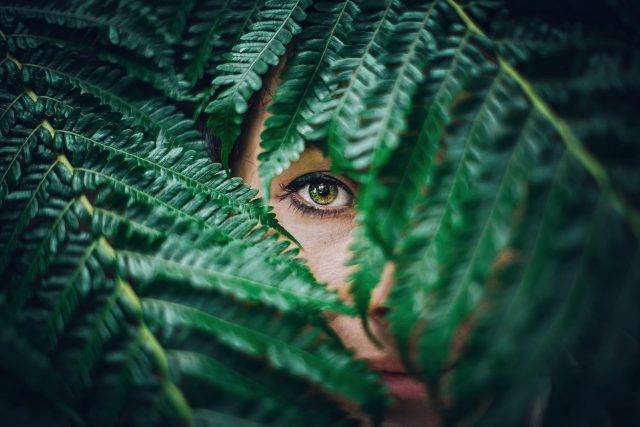 optometrist, woman showing single green eye through leaves in Tulsa, OK