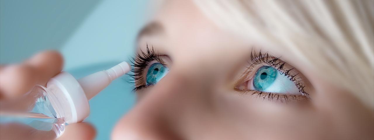 Eye doctor, woman applying eye drops in Kenneth Square, PA