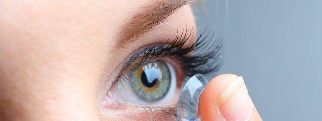 Optometrist, woman putting on a contact lens in Boston, Braintree, Burlington, Danvers, Dorchester, Leominster, Marlborough, Quincy, Worcester & Webster MA