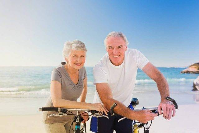 Old couple cycling by the sea, maintaining active lifestyle despite age related macular degeneration risk