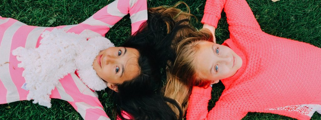 Young Girls Laying on Grass 1280x480 1024x384