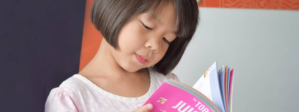 Asian girl reading in Sugar Land, TX