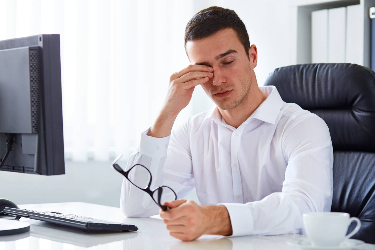 man rubbing dry eyes