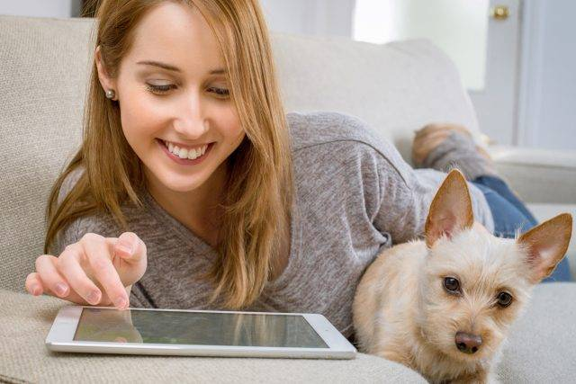 gal and her dog, happily using an iPad - digital eyestrain Jacksonville