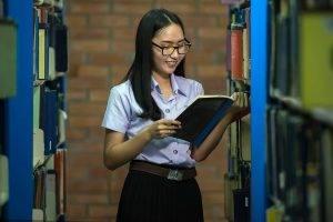 Eye doctor, asian girl reading in a library in Atlanta, GA