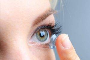 Eye doctor, woman putting on a contact lens in Atlanta, GA