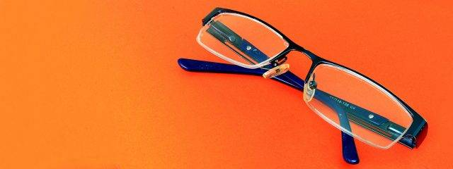 Eye doctor, pair of eyeglasses on orange surface in Toronto, ON