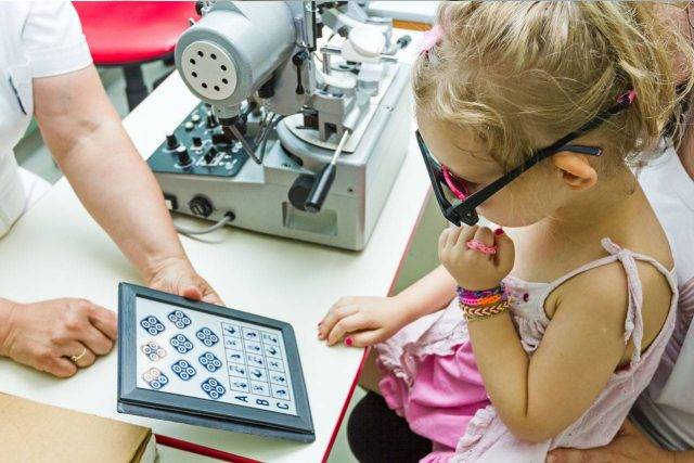 Child reading eye test card