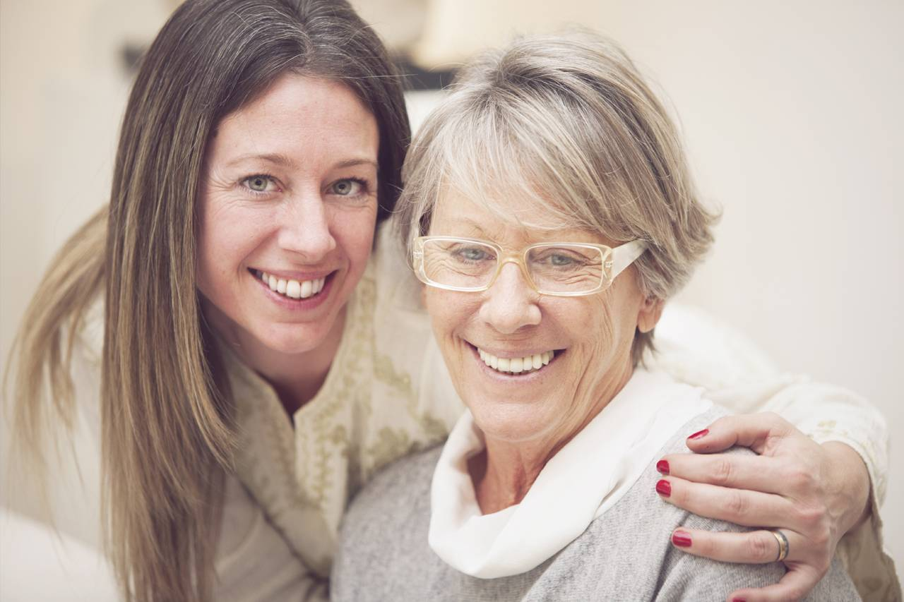 older woman wearing eyeglasses, with daughter wearing contacts