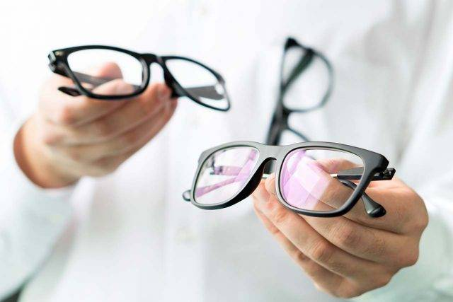 optician holding eyeglasses near you