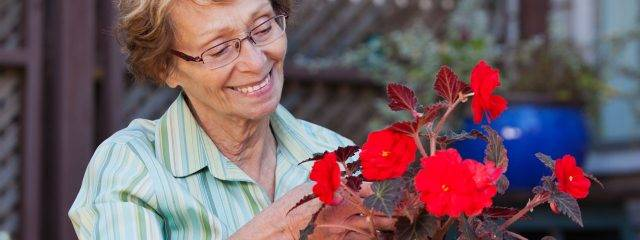 Optometrist, senior woman looking at a bouquet of flowers in Redondo Beach, CA