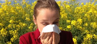 Woman sneezing, surrounded by flowers, eye allergies - Optometrist - Parker, CO