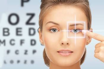 blonde woman putting in contacts in front of eye exam chart in Orange