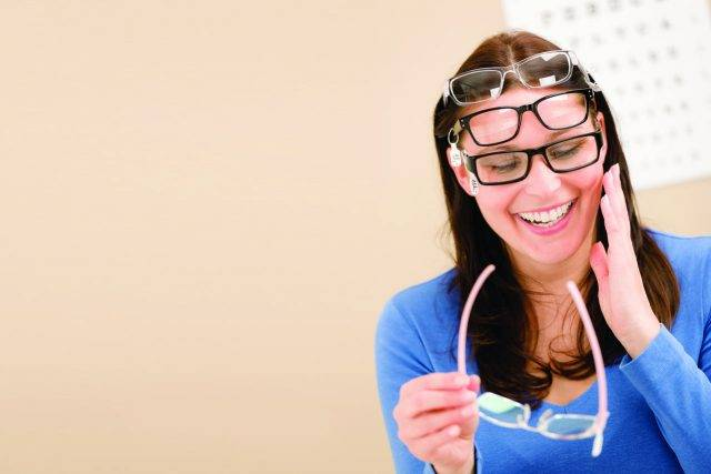 Woman wearing multiple pair of eyeglasses in Madison, WI