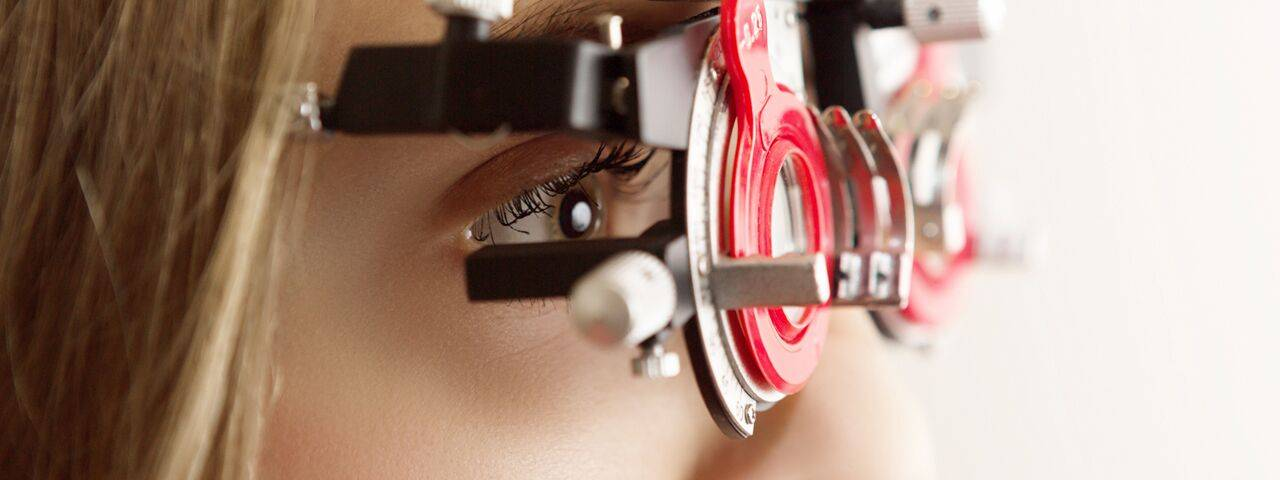 Optometrist, woman using a phoropter in Coral Gables, FL