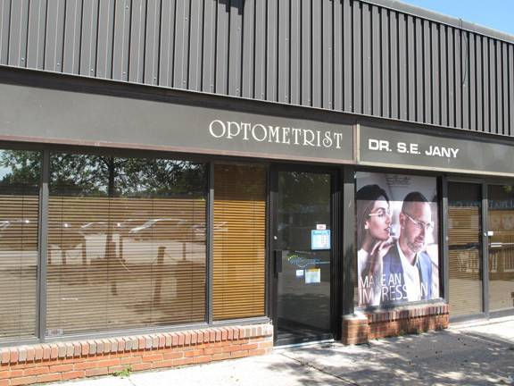 Photo of exterior front of office. Sign reads Optometrist- Dr. S.E. Jany