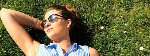 Eye doctor,  woman wearing sunglasses, sitting on the grass in Costa Mesa, CA