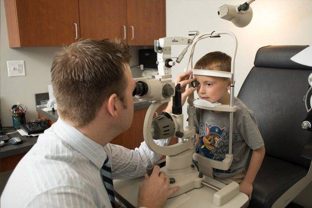 Eye doctor, boy at an eye exam in Winnipeg, Manitoba