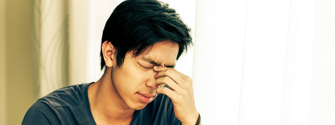 Asian man rubbing his eyes in Carrollton, TX