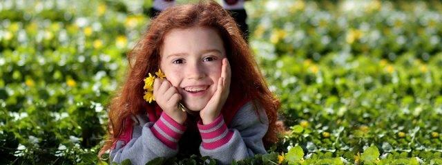 Eye doctor, little girl sitting on the grass in Carrollton, TX