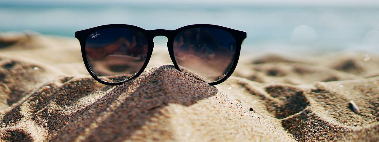 Pair of sunglasses on sand in Hemlock and Saginaw, MI