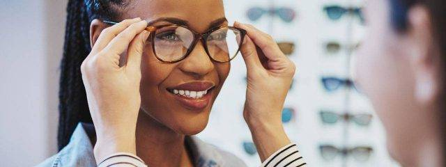 Eye doctor, african american woman trying a new pair of eyeglasses in Irvine & Laguna Beach, CA