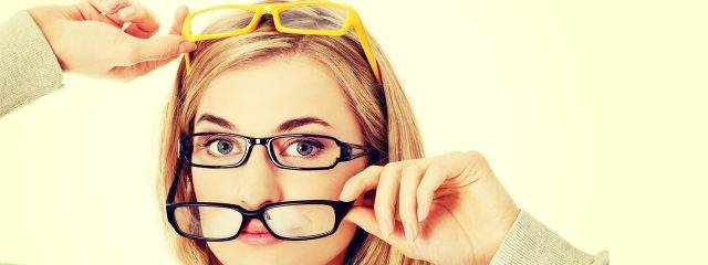 Eye doctor, woman wearing multiple pairs of eyeglases in Irvine & Laguna Beach, CA
