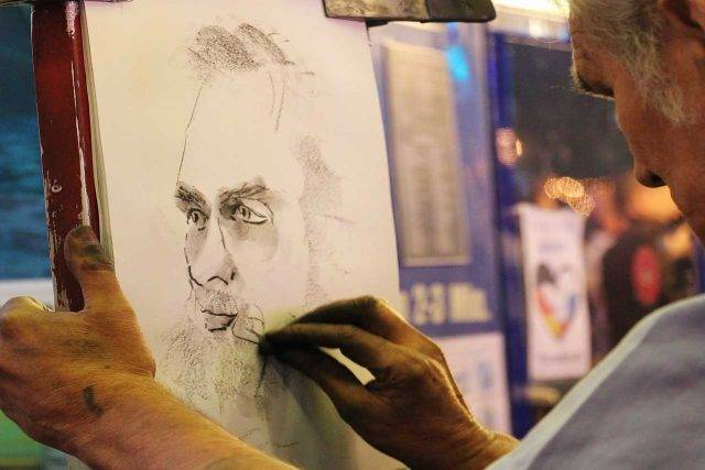 artist drawing man with no glasses