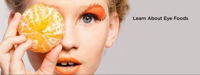 Optometrist, woman holding an orange over her eye in Cincinnati, OH