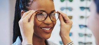 woman trying on glasses, eye doctor, Akron, OH