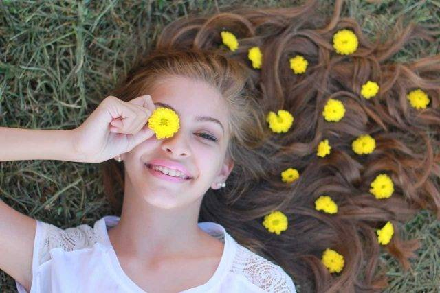girl with flowers in here hair and smiling